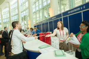 Volunteers assist at the registration desk for attendees picking up their packets.