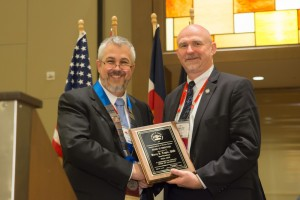 President Dan Martell presents a service plaque to Past President Barry Logan during the Annual Business Meeting.