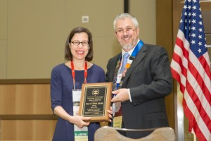Jane Lewis receives a plaque from President Daniel Martell after completing her term on the AAFS Board of Directors.