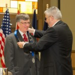 Victor Weedn accepts the President's Chain of Office from President Daniel Martell during the 2015 Annual Business Meeting.