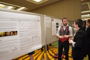 A poster presenter explains his research during the Poster Session.