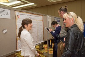 A poster presenter enjoys the process of explaining a case study.
